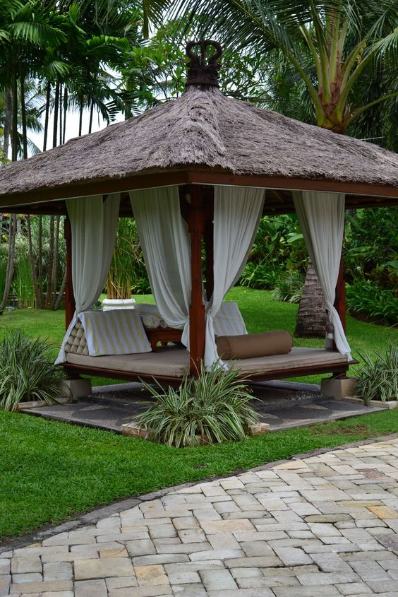 Bali inspired hut with dried thatches roofs wood floors and solid wood pillars