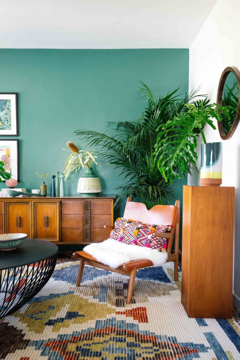 Caribbean like oasis green wall potted plants wooden console table and nightstand textural color area rug