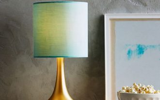 Fumi bedside lamp with gold tone base and blue shade