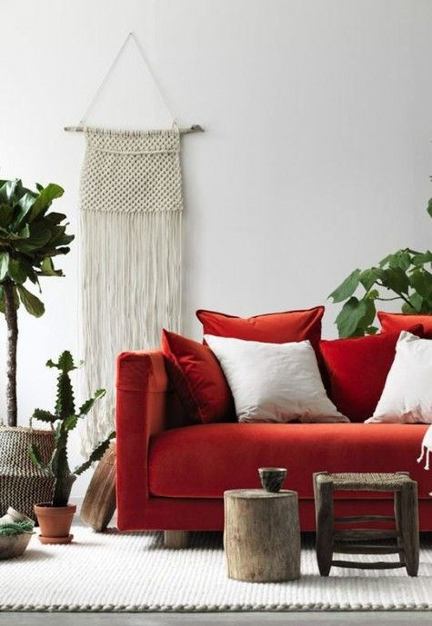 Minimalist Boho living room bold orange soda white and red throw pillows dark wood log table and stool Boho wall decor in white