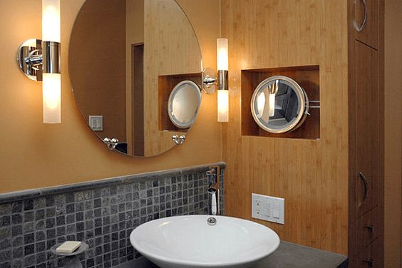 a couple of tubular sconces round shape mirror concrete mosaic tile backsplash