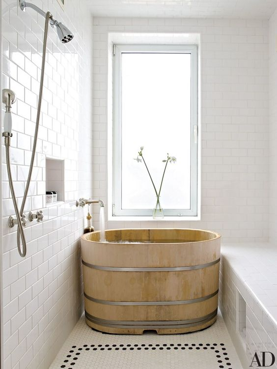 airy and bright bathroom Japanese soak bathtub made of wood white ceramic subway tile walls mosaic tile floors in white stainless steel showerhead centered glass window