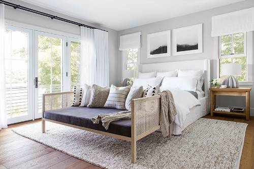 airy bedroom white bedding treatment wood banquette with gray cushion and throw pillows white rug wood bedside table wood floors