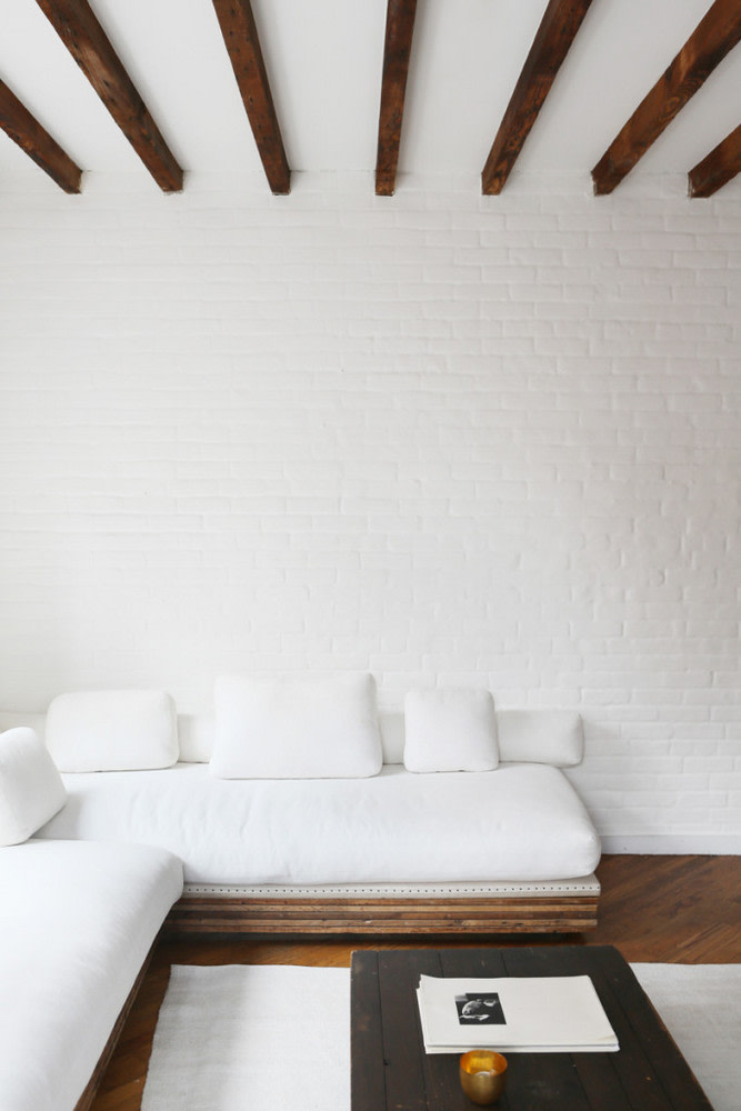 airy & clean look living room white brick walls white ceilings with exposed wood beams darker wood floors minimalist sectional with wood base and white cushions black painted wood coffee table
