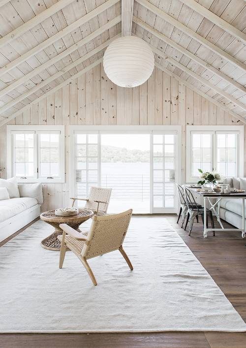 airy living room exposed wood beams and roofs big lantern like pendant wicker chairs with wood structure wicker coffee table modern white sofa white area rug wood floors