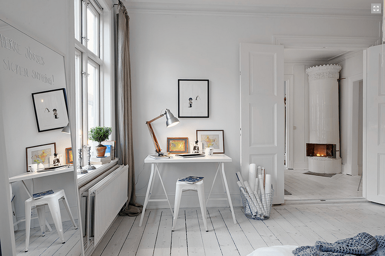 all white bedroom with a tiny working desk in white white stool industrial table lamp white wood plank floors white walls