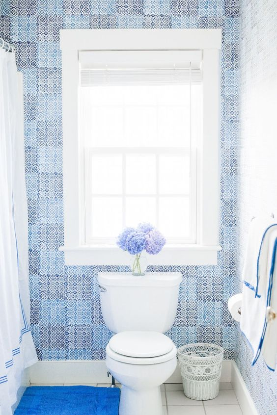 blue lavender mosaic tile walls white ceramic tile floors white toilet white trash bag well lighted window