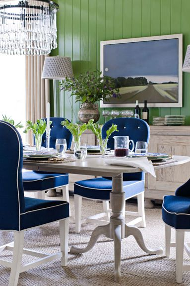 bright blue dining chairs green wood planked walls white dining table crystal chandelier