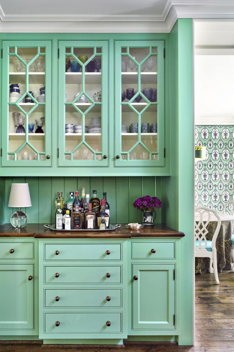 cool green buffet with glass door and dark countertop