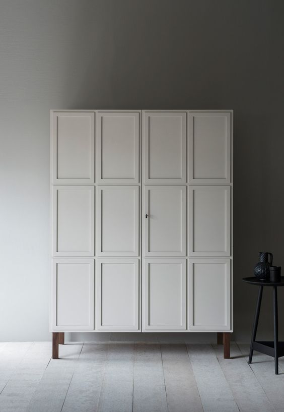 door panelled armoire in white with wood legs black side table with round top