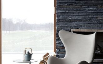 egg chair in white white side table with round top cozy white area rug textured stone fireplace's mantel and walls
