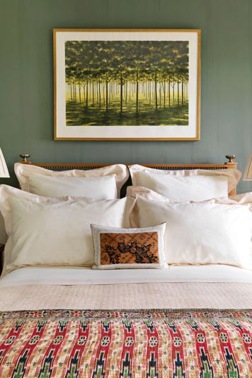 forest painting in yellow and green gray wall painting white bed linen Indonesian comforter
