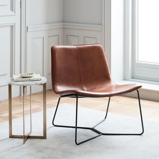 gloss leather armchair by West Elm supported with tiny metal legs