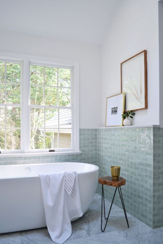 green sage tile walls with gloss surface white walls white bathtub with white throw blanket hairpin leg stool with wood top