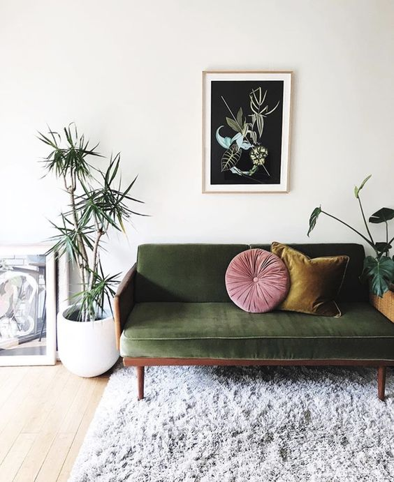 green velvet sofa yellow and pink throw pillows white potted houseplants wooly white area rug
