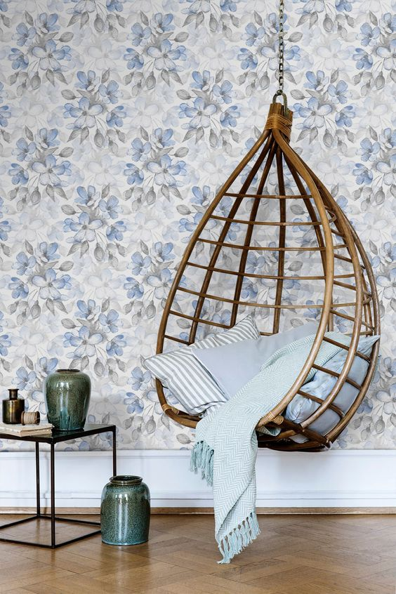 hanging rattan chair in semi egg shape flower wallpaper in light blue glass top side table with metal structure