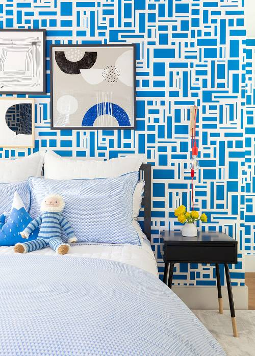 kid's room blue wallpaper with modern patterns in white black framed abstract paintings midcentury modern bedside table in black light blue comforter white bed linen