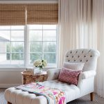 Large Reading Corner Lounge Chaise With White Tufted Upholstery Cheerful Pattern Throw Blanket And Pillows Moroccan Wood Side Table Striped & Textured Area Rug White Window Curtains