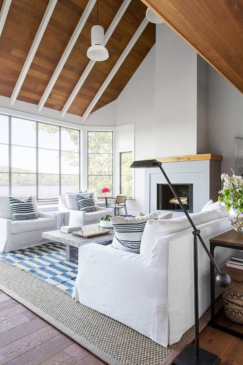 main living room modern clean line fireplace with white mantel white sofa slipcovers blue white area rug white wood beams wood roofs wood floors