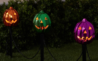 metallic grinned pumpkin pathway lamps in purple green and gold