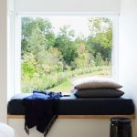 Minimalist Reading Nook Built In Bench Seat With Deep Blue Covered Mattress Addition Fur Throw Mat Black Ceramic Side Table Light Wood Floors Glass Window