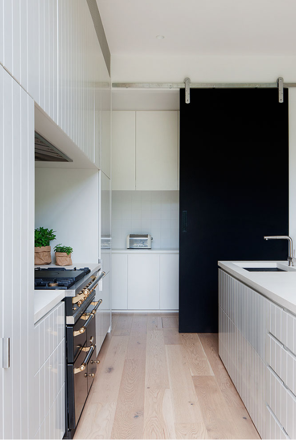 modern minimalist kitchen hidden storage pieces behind the black sliding door