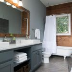 Modern Rustic Bathroom Shiplap Accent Wall Gray Painted Walls Wood Framed Mirror Marble Countertop Gray Painted Cabinets Herringbone Wood Floors Farmhouse Style Shower Curtains In White