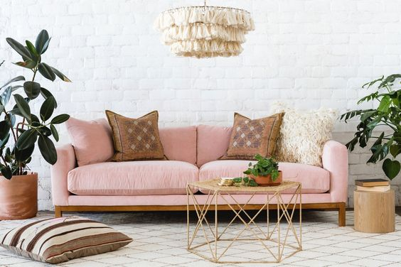 modern sofa with soft baby pink cushion and pine legs brass base coffee table houseplants with pot log stool floor pillow