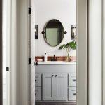 Neutral Tone Vanity Bathroom Gray Cabinets Wood Backsplash Oval Shape Wall Mirror Greenery With Glass Pot