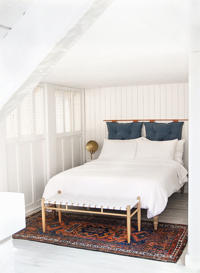 scandinavian bed frame with elevated headboard bench bed with leather seater vintage rug with bold pattern and color