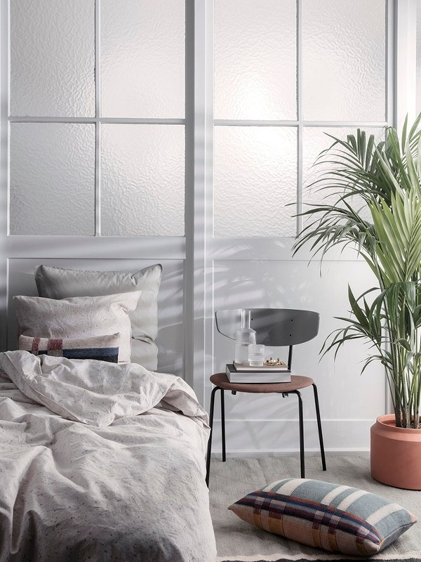 scandinavian style bedroom white bed linen and pillowcases scandinavian chair as the bedside table floor pillow in dominant gray plants in burnt clay planter