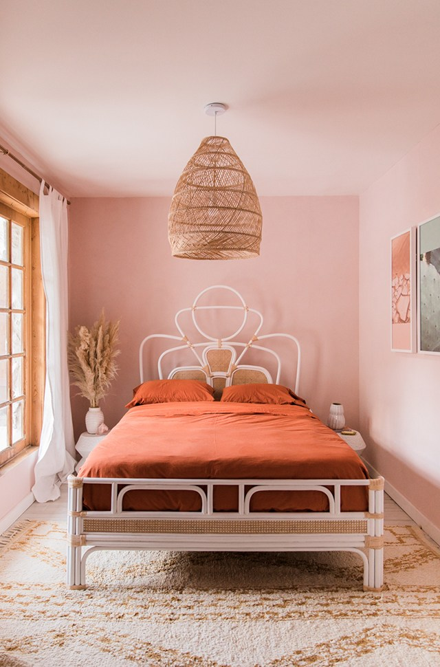soft pink walls warm orange bed linen and pillowcovers classic bed frame with curly headboard soft tone shag rug extra large pendant with fish trap lampshade
