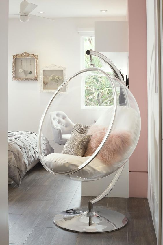 transparent egg chair with throw pillows and stainless steel base