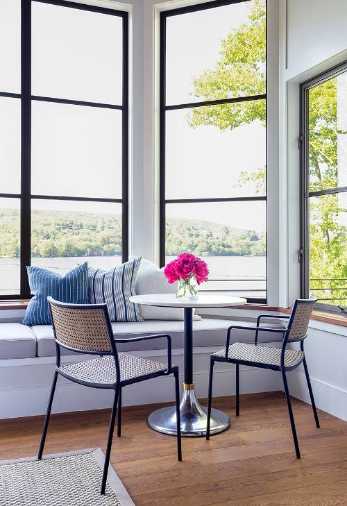 waterfront spot large glass windows with black trims built in bench seat with cushion a couple of wicker chairs with tiny metal frames round top table with metal base
