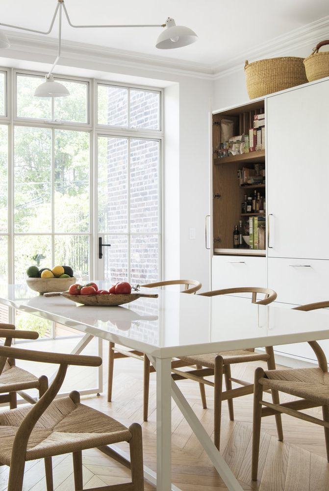 white cabinetry behind the glass door white top dining table wood dining chairs