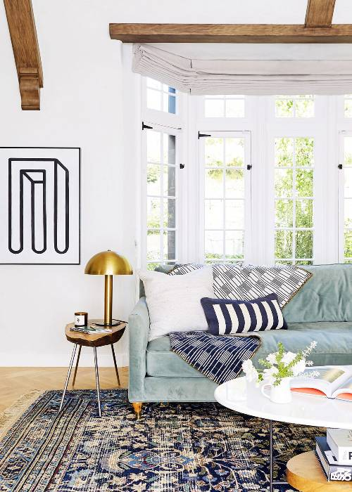 white crisp walls with modern wall decor in black velvet sofa in light blue throw pillows throw blanket log top side table with tripod legs gold tone table lamp oval top coffee table vintage area rug