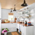 Wide And Open Pantry In White Wood Color Kitchen Countertop White Kitchen Cabinetry Stone Tile Floors Earthy Brown Mat Colorful Flowers On White Pot