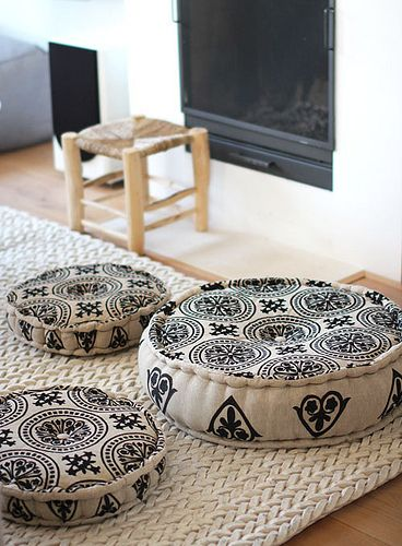 Moroccan floor cushions with bold black patterns white woven area rug