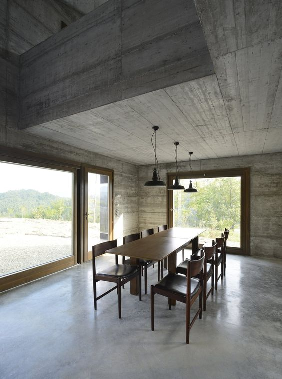 airy industrial dining room industrial pendants dark tone wood dining set gloss concrete floors traditional concrete walls oversized glass windows and door