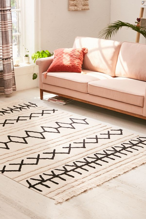 area rug with graphic prints in black and fringed trims at two bottom sides