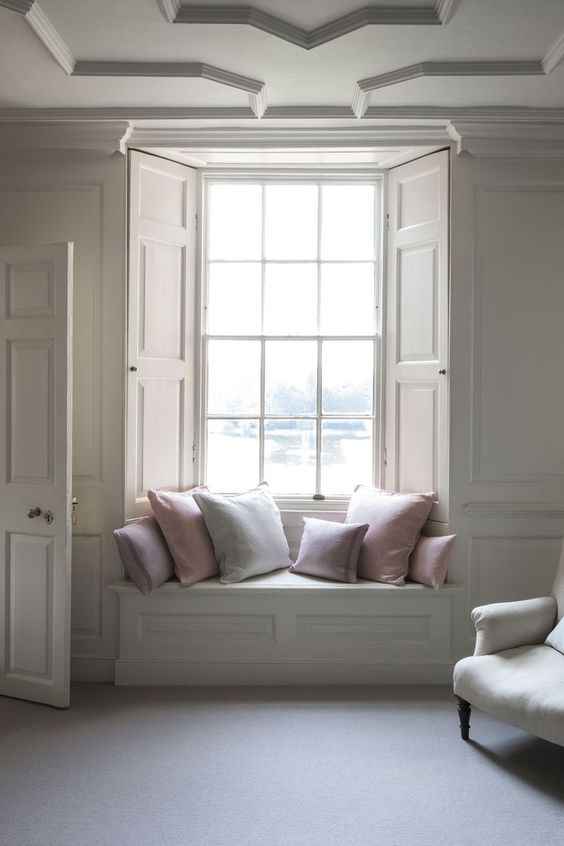 bay window with wood panel shutters in white and trimmed glass for the first layer built in bench seat with throw pillows
