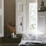 Crisp White Window Shutter Made Of Solid Wood Crisp White Bed Linen And Shams Dark Gray Duvet Cover Black Stool Bedside Table With Round Top