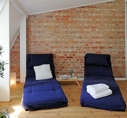 floor cushions in navy blue throw pillows in white brick walls light wood floors