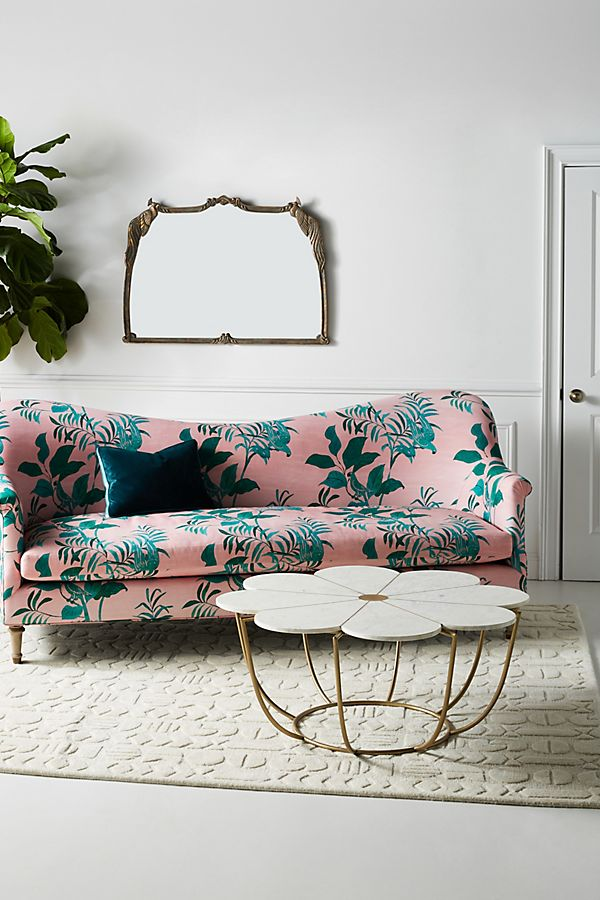 flower top coffee table with brass legs textured area rug in white vintage style sofa in pink with blue floral motifs
