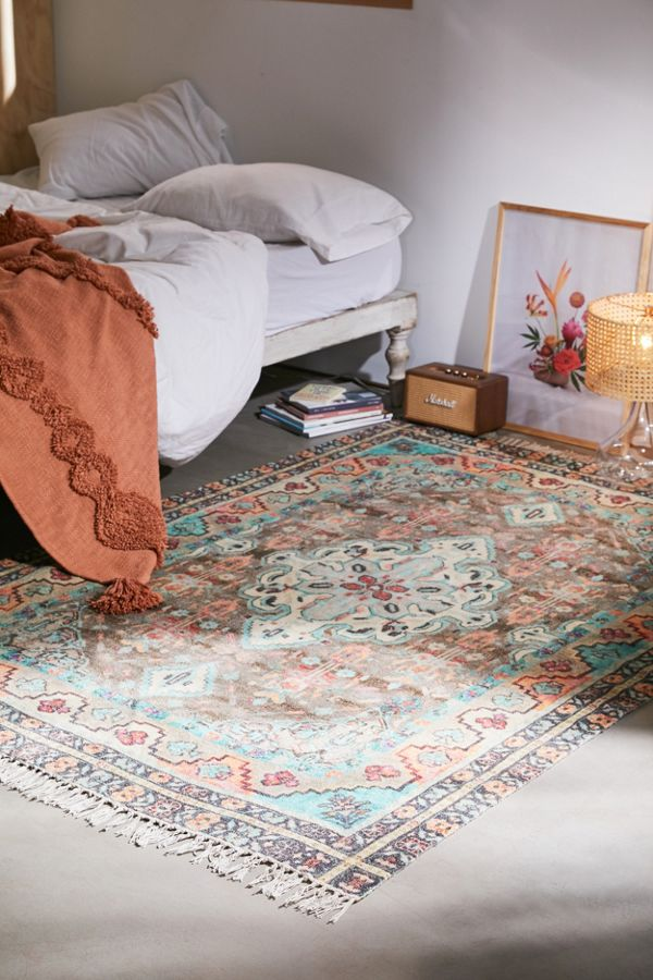 old and worn out area rug with central prints and fringed edges
