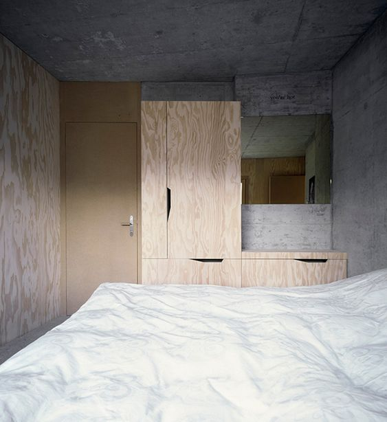 plywood walls and cabinets hard concrete ceiling and wall white duvet cover