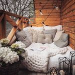 Rustic Boho Balcony Idea Wood Planked Walls And Ceilings Wood Railing System Cushion With Throw Pillows And Knitted Wool Blanket String Lights