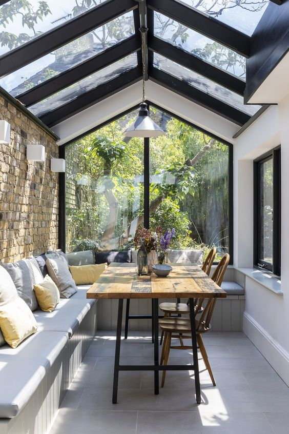 semi outdoor kitchen and dining space glass ceilings with wood beams L shaped built in bench with gray cushion yellow throw pillow wood dining table wood dining chairs