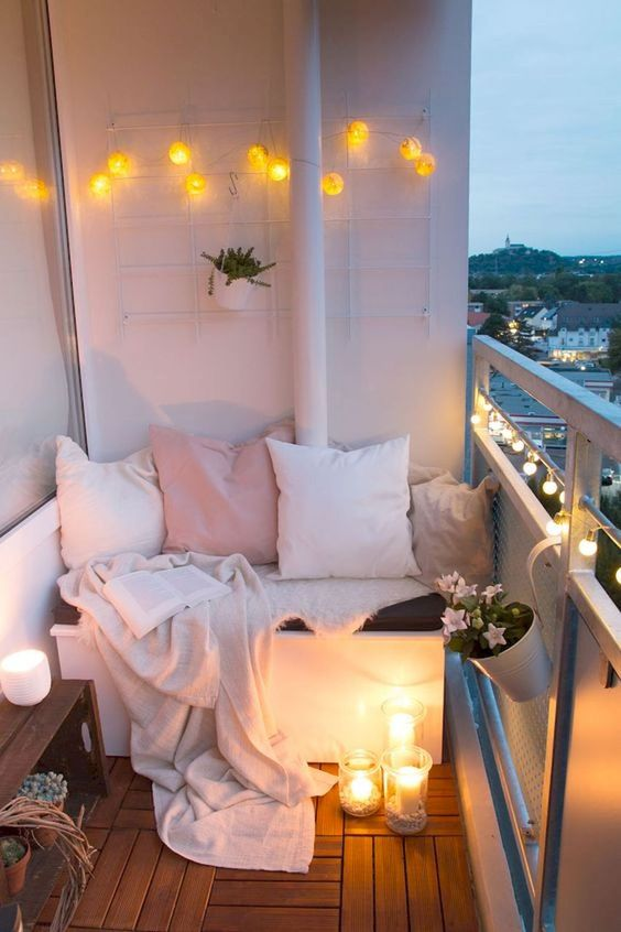 small balcony for apartment white cushion white and pink throw pillows white throw blanket floor candle lightings string of orbs on walls