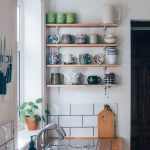 Small Kitchen For Apartment Wood Wall Mounted Shelving Units For Display Wood Countertop Stainless Steel Sink And Faucet White Subway Ceramic Tile Backsplash